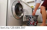 Купить «Man putting his clothes into washing machine», видеоролик № 29689397, снято 26 августа 2016 г. (c) Wavebreak Media / Фотобанк Лори