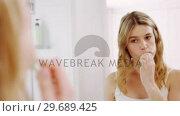 Купить «Woman looking in mirror while brushing her teeth in bathroom», видеоролик № 29689425, снято 26 августа 2016 г. (c) Wavebreak Media / Фотобанк Лори