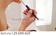 Купить «Woman applying make-up on her face in bathroom», видеоролик № 29689429, снято 26 августа 2016 г. (c) Wavebreak Media / Фотобанк Лори