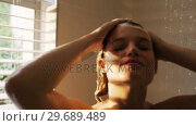 Купить «Woman taking a shower in bathroom», видеоролик № 29689489, снято 26 августа 2016 г. (c) Wavebreak Media / Фотобанк Лори
