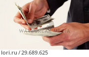 Купить «Mid-section of man counting hundred dollar note», видеоролик № 29689625, снято 24 августа 2016 г. (c) Wavebreak Media / Фотобанк Лори