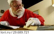 Купить «Santa claus reading a book», видеоролик № 29689721, снято 6 июня 2016 г. (c) Wavebreak Media / Фотобанк Лори