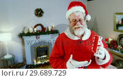 Купить «Santa claus holding a gift box», видеоролик № 29689729, снято 6 июня 2016 г. (c) Wavebreak Media / Фотобанк Лори
