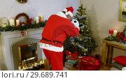 Купить «Santa claus placing gift near christmas tree», видеоролик № 29689741, снято 6 июня 2016 г. (c) Wavebreak Media / Фотобанк Лори