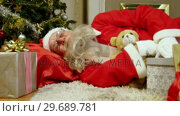 Купить «Santa claus sleeping with christmas gifts and teddy bear», видеоролик № 29689781, снято 6 июня 2016 г. (c) Wavebreak Media / Фотобанк Лори
