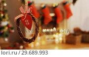 Купить «Christmas grapevine wreath with ribbon hanging on window», видеоролик № 29689993, снято 31 августа 2016 г. (c) Wavebreak Media / Фотобанк Лори