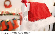 Купить «Santa hat and christmas decoration hanging on chair», видеоролик № 29689997, снято 31 августа 2016 г. (c) Wavebreak Media / Фотобанк Лори