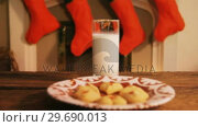 Купить «Gingerbread cookies with a glass of milk on wooden table», видеоролик № 29690013, снято 31 августа 2016 г. (c) Wavebreak Media / Фотобанк Лори