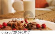 Купить «Christmas cookies on plate with a glass of milk», видеоролик № 29690017, снято 31 августа 2016 г. (c) Wavebreak Media / Фотобанк Лори