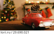 Купить «Toy car with pine cone on wooden table», видеоролик № 29690021, снято 31 августа 2016 г. (c) Wavebreak Media / Фотобанк Лори