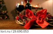 Купить «Grapevine wreath with red ribbon and pine cone», видеоролик № 29690053, снято 31 августа 2016 г. (c) Wavebreak Media / Фотобанк Лори