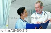 Купить «Doctor discussing reports with colleague», видеоролик № 29690313, снято 11 сентября 2016 г. (c) Wavebreak Media / Фотобанк Лори