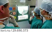 Купить «Surgeons and nurse looking at x-ray», видеоролик № 29690373, снято 11 сентября 2016 г. (c) Wavebreak Media / Фотобанк Лори