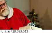 Купить «Santa claus checking a gift box and smiling», видеоролик № 29693013, снято 6 сентября 2016 г. (c) Wavebreak Media / Фотобанк Лори