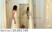 Beautiful woman trying on wedding dress in a shop. Стоковое видео, агентство Wavebreak Media / Фотобанк Лори