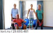 Купить «Trainer assisting senior citizens in performing stretching exercise», видеоролик № 29693481, снято 27 апреля 2016 г. (c) Wavebreak Media / Фотобанк Лори