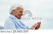 Купить «Senior woman using mobile phone on beach», видеоролик № 29693597, снято 29 сентября 2016 г. (c) Wavebreak Media / Фотобанк Лори