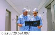 Купить «Surgeon and colleague discussing over an x-ray», видеоролик № 29694897, снято 10 сентября 2016 г. (c) Wavebreak Media / Фотобанк Лори