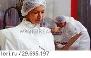Female butcher writing on clipboard. Стоковое видео, агентство Wavebreak Media / Фотобанк Лори