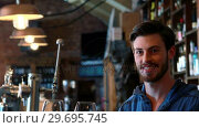 Купить «Portrait of barman holding two glasses of red wine at bar counter», видеоролик № 29695745, снято 14 ноября 2016 г. (c) Wavebreak Media / Фотобанк Лори