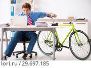 Купить «Young businessman using bike to commute to the office», фото № 29697185, снято 30 августа 2018 г. (c) Elnur / Фотобанк Лори