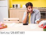 Купить «Young man calculating expences for vegetables in kitchen», фото № 29697661, снято 3 августа 2018 г. (c) Elnur / Фотобанк Лори