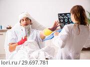 Купить «Young doctor examining injured patient», фото № 29697781, снято 2 октября 2018 г. (c) Elnur / Фотобанк Лори