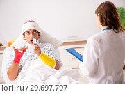 Купить «Young doctor examining injured patient», фото № 29697797, снято 2 октября 2018 г. (c) Elnur / Фотобанк Лори