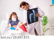 Купить «Young doctor examining injured patient», фото № 29697813, снято 2 октября 2018 г. (c) Elnur / Фотобанк Лори