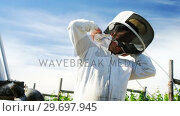 Купить «Beekeeper wearing protective mask in apiary», видеоролик № 29697945, снято 27 октября 2016 г. (c) Wavebreak Media / Фотобанк Лори