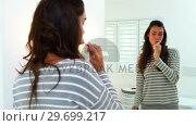 Купить «Woman brushing his teeth in bathroom», видеоролик № 29699217, снято 29 ноября 2016 г. (c) Wavebreak Media / Фотобанк Лори