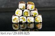 Купить «Stack of maki sushi on black background», видеоролик № 29699825, снято 8 декабря 2016 г. (c) Wavebreak Media / Фотобанк Лори