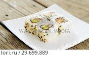 Купить «Uramaki sushi served on plate against wooden background», видеоролик № 29699889, снято 8 декабря 2016 г. (c) Wavebreak Media / Фотобанк Лори