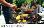 Купить «Mid section of man grilling corn, meat and vegetable on barbecue», видеоролик № 29700397, снято 1 февраля 2017 г. (c) Wavebreak Media / Фотобанк Лори