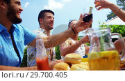 Купить «Group of happy friends toasting beer bottles and glasses at outdoors barbecue party», видеоролик № 29700405, снято 1 февраля 2017 г. (c) Wavebreak Media / Фотобанк Лори