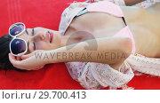 Купить « Woman enjoying sunbath on the pool edge», видеоролик № 29700413, снято 1 февраля 2017 г. (c) Wavebreak Media / Фотобанк Лори