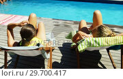 Two womens interacting with each other while sunbathing near swimming pool. Стоковое видео, агентство Wavebreak Media / Фотобанк Лори