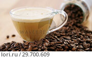 Cup of coffee with spilled roasted beans. Стоковое видео, агентство Wavebreak Media / Фотобанк Лори