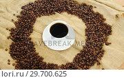 Купить «Cup of coffee surrounded with roasted beans», видеоролик № 29700625, снято 6 октября 2016 г. (c) Wavebreak Media / Фотобанк Лори
