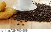 Купить «Coffee with roasted coffee beans and croissant», видеоролик № 29700689, снято 6 октября 2016 г. (c) Wavebreak Media / Фотобанк Лори