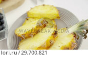 Купить «Slices and halved pineapples in plate», видеоролик № 29700821, снято 19 декабря 2016 г. (c) Wavebreak Media / Фотобанк Лори