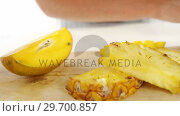 Купить «Slices and halved pineapple kept on chopping board», видеоролик № 29700857, снято 19 декабря 2016 г. (c) Wavebreak Media / Фотобанк Лори