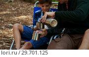 Купить «Father and son having coffee outside tent», видеоролик № 29701125, снято 2 марта 2017 г. (c) Wavebreak Media / Фотобанк Лори