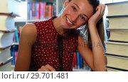 Купить «Attentive schoolgirl reading book in library», видеоролик № 29701481, снято 19 ноября 2016 г. (c) Wavebreak Media / Фотобанк Лори