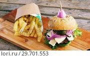 Купить «Hamburger and french fries on wooden board», видеоролик № 29701553, снято 13 января 2017 г. (c) Wavebreak Media / Фотобанк Лори