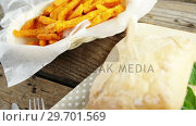 Купить «Hamburger and french fries on wooden table», видеоролик № 29701569, снято 13 января 2017 г. (c) Wavebreak Media / Фотобанк Лори