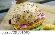 Купить «Hamburger and french fries on wooden board», видеоролик № 29701585, снято 13 января 2017 г. (c) Wavebreak Media / Фотобанк Лори