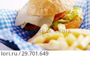 Купить «Burger and french fries on table», видеоролик № 29701649, снято 13 января 2017 г. (c) Wavebreak Media / Фотобанк Лори