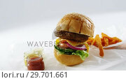 Купить «Hamburger and french fries on table», видеоролик № 29701661, снято 13 января 2017 г. (c) Wavebreak Media / Фотобанк Лори