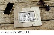 Купить «Photo frame, sunglasses and mobile phone on wooden plank», видеоролик № 29701713, снято 13 января 2017 г. (c) Wavebreak Media / Фотобанк Лори